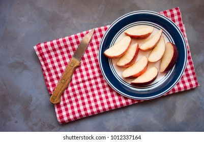 Sliced apples on a plate sitting on a red and white gingham napkin with an old knife with wooden handle.