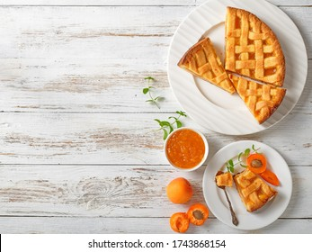 sliced apricot shortcrust pie with a lattice pie crust topping on white plates on a rustic wooden table, flat lay, free space