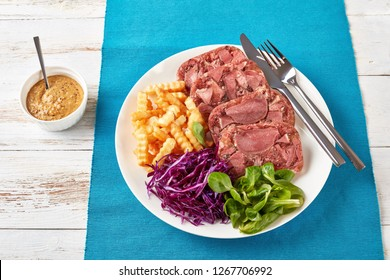 sliced aspic of beef tongue served with french fries, green leaves and red cabbage salad on a white plate on a wooden table with mustard in a bowl, view from above, close-up
