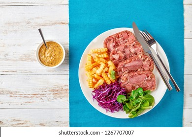 sliced aspic of beef tongue served with french fries, green leaves and red cabbage salad on a white plate on a wooden table with mustard in a bowl, view from above