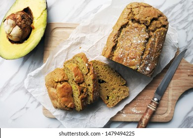 Sliced avocado bread loaf (avocado pound cake, bread made of avocado)on white parchment paper. Marble table. Wooden cutting board. Half cut avocado. wood handle knife.
