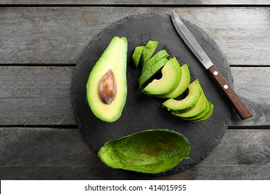 Sliced avocado with knife on slate plate