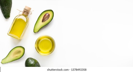 Sliced avocadoes and oil in bowl and bottle on white background top view, copy space. Vegetarian oils concept