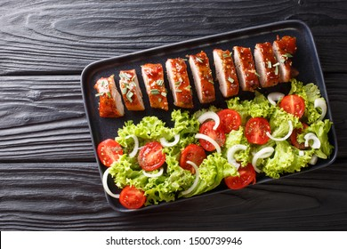 Sliced baked pork tenderloin in honey-garlic sauce with a side dish of vegetable salad close-up on a plate on the table. horizontal top view from above