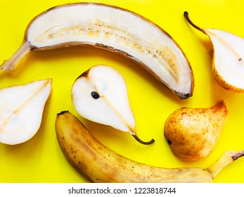 Sliced banana and pears on bright yellow background