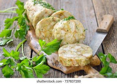 Sliced Bavarian bread dumpling, the perfect side dish for roasts or strips of meat with sauce, served on a wooden cutting board with parsley leaves