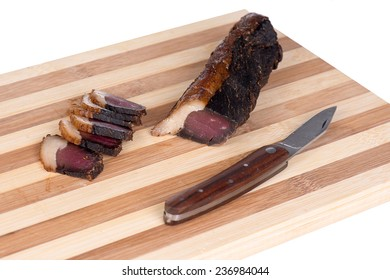 Sliced beef jerky or biltong with fat on a wooden board with a pocket knife