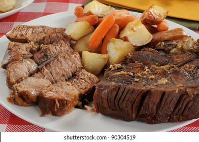 A sliced beef pot roast with autumn vegetables
