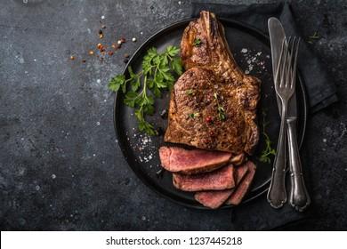 sliced beef steak on black plate, dark background, top view, copy space