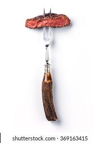 Sliced beef steak ribeye on meat fork on white background