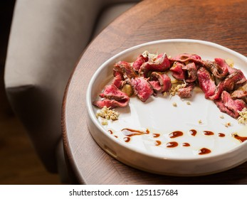 sliced beef steak, salad and glass of red wine on a Wooden table in a restaurant