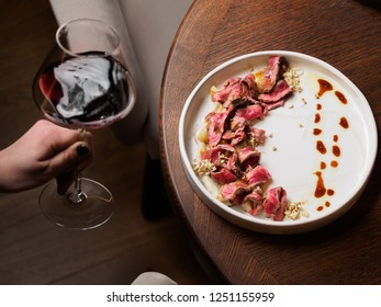 Sliced beef steak with sauce on round white plate with wine on wooden table, glass of red wine in female hand