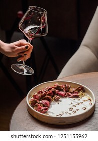 Sliced beef steak with sauce on round white plate with wine on wooden table, glass of red wine in female hand, Vertical photo