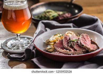 Sliced Beef tenderloin roasted steak potatoes rosemary and draft beer.
