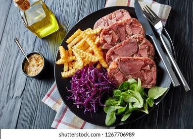 sliced beef tongue aspic served with french fries, green leaves and red cabbage salad on a black plate on a wooden table with mustard in a bowl, view from above, close-up