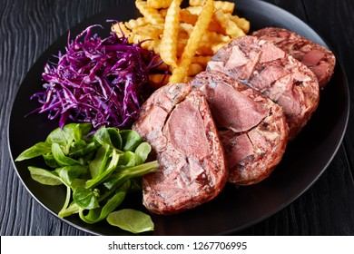 sliced beef tongue and meat aspic served with french fries, green leaves and red cabbage salad on a black plate on a wooden table, view from above, close-up