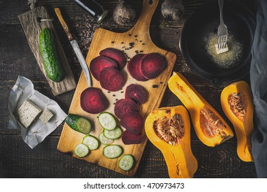 Sliced beet with vegetable and  pan with butter on the wooden table top view