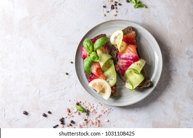 Sliced beetroot marinated salmon sandwiches with rye bread, cucumber, basil and lemon served on ceramic plate over grey texture background. Top view, copy space