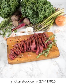 Sliced Bison Loin Tri Tip Steak on Wooden Board