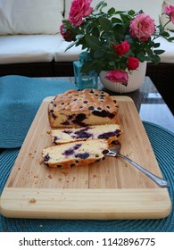 Sliced blueberry cake on a wooden board and vintage spoon. Side view. Fresh homemade pastry with berries.