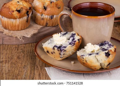 Sliced blueberry muffin and butter with a cup of coffee on a plate