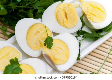Sliced boiled eggs on long white plate. Close up.