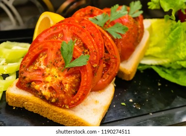 Sliced bread , baked tomatoes and fresh parsley and salad on a table