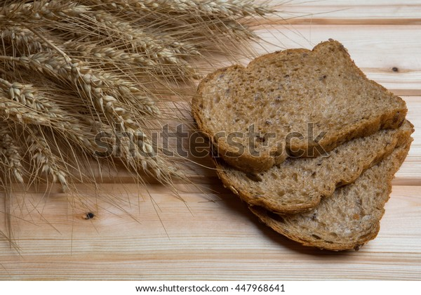 Sliced bread with ears of corn on the wooden background