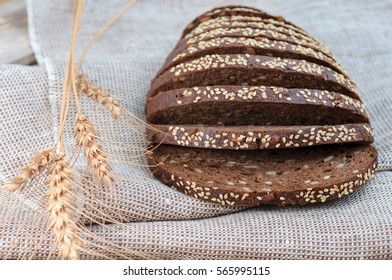 sliced bread with ears of rye and wheat on the wooden background