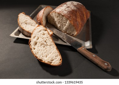 sliced bread with a knife on a dark background