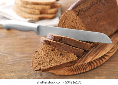 Sliced bread and knife on wooden cutting board closeup