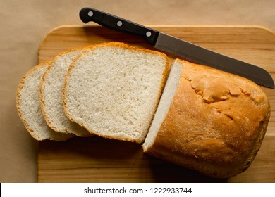 Sliced bread loaf and knife on cutting board. Top down view.