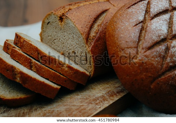 Sliced bread rye on cutting board closeup on wooden background