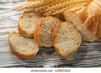 Sliced bread wheat ears on wooden surface.