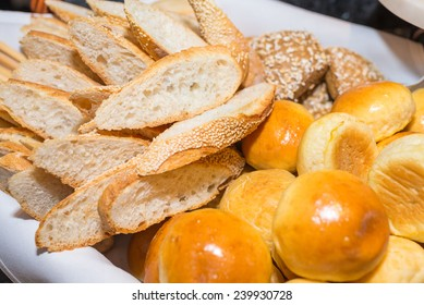 Sliced breads and buns served on white plate