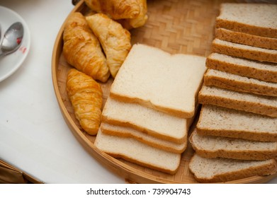 Sliced breads and Croissant lay on a wooden tray,whole wheat breads lay on wooden tray