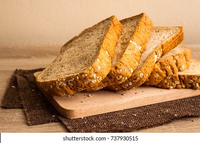 Sliced breads put on wooden plate,wholewheat breads lay on wood plate and put on sackcloth,whole wheat breads