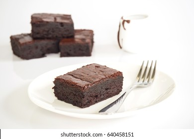 Sliced brownies on white plate over white background. Served with chocolate fudge in jar. Favorite chocolate dessert for chocolate lover. Sweet and moist of cocoa taste.