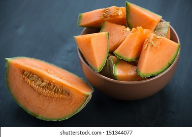Sliced cantaloupe melon, dark wooden background