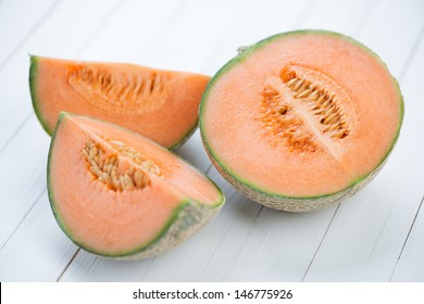 Sliced cantaloupe melon on wooden boards, studio shot