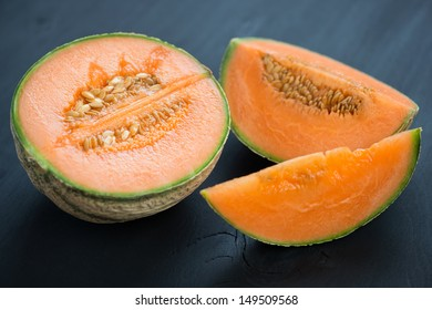 Sliced cantaloupe on black wooden background