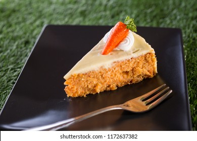 Sliced Carrot cake, homemade bekery on black dish with fork, copy space