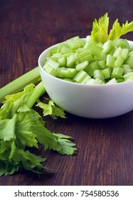 Sliced celery stalk in a white bowl on a wooden table. Healthy food close-up.