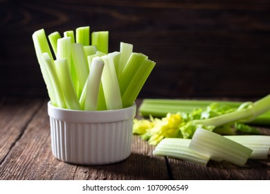 Sliced celery in a white bowl on a wooden background