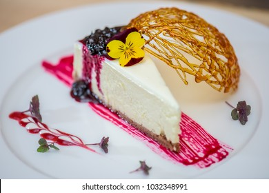 Sliced cheese cake and edible flowers on a white plate