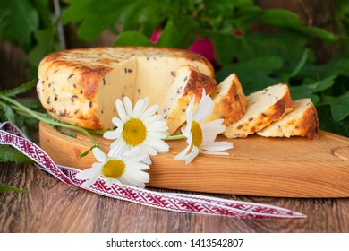 sliced cheese with cumin on a wooden table. Celebration of a traditional holiday in Latvia Ligo in June