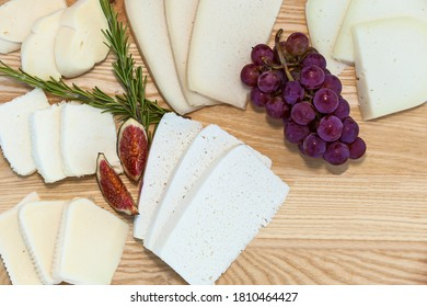 Sliced cheese of different varieties of grapes and figs on the background of a wooden board