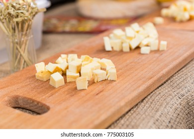 Sliced cheese on a wooden board in the kitchen. Food and beverages concept