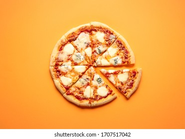 Sliced cheese pizza on an orange background above view. Pizza sliced in eight. Delicious homemade pizza top view. Pizza made only with cheese and tomato sauce.