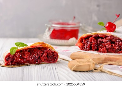 Sliced cherry strudel on a wooden board